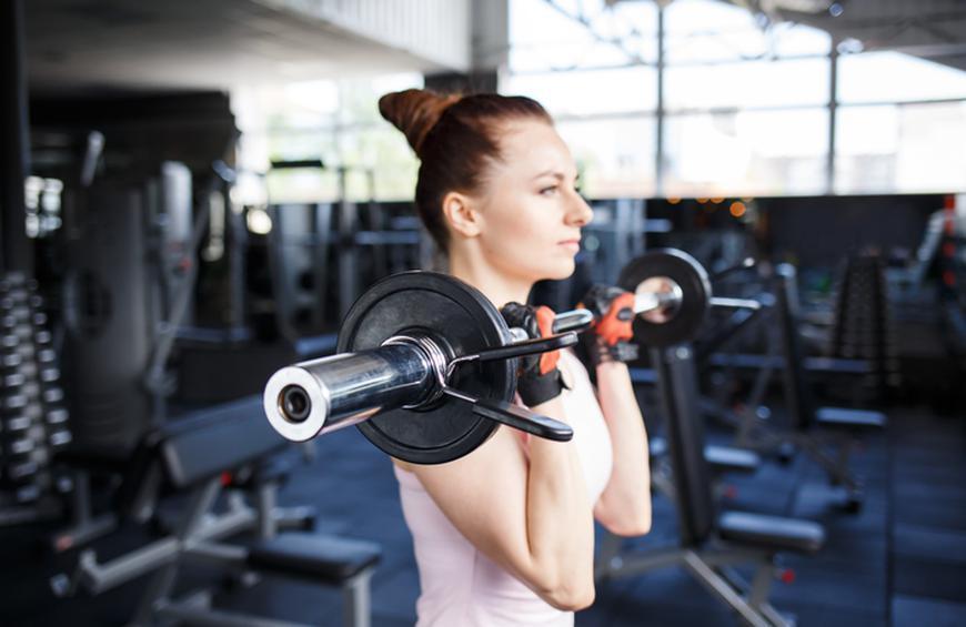زن ورزشکار در حال تمرین با هالتر