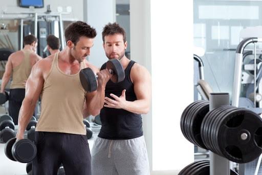 ورزشکار و مربی مرد در حال تمرین با دمبل سنگین